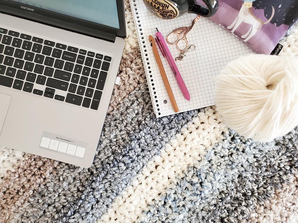 laptop, bamboo crochet hook, pink pen, scissors, tarn, dog bag, and graph notebook all on a blanket.