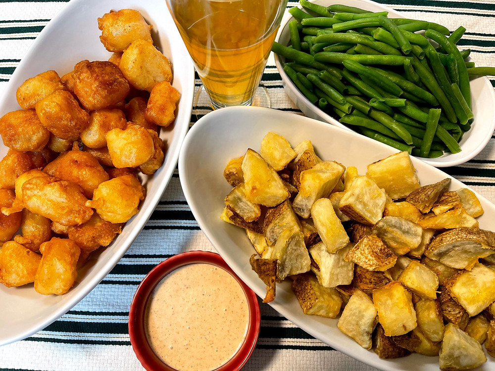 Image of mini beer batter fried fish, remoulade sauce, a light ale beer, green beans, and cubed fried potatoes (known as Patatas Bravas).