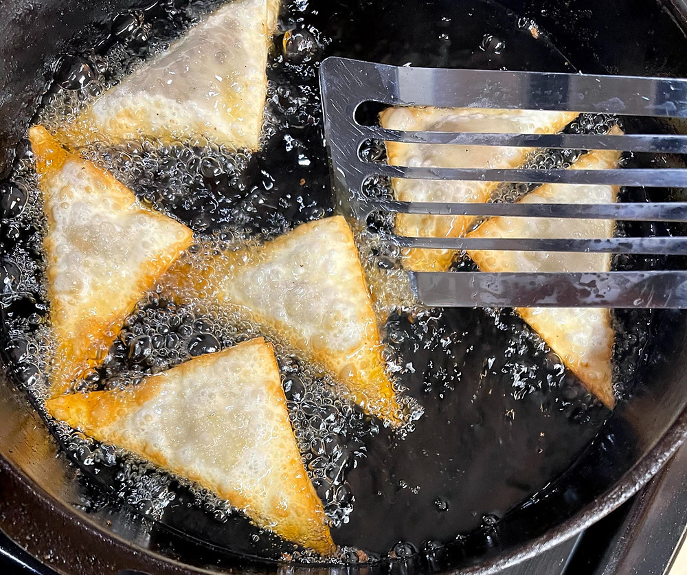 Image of wontons frying, golden around the edges, but the side up is still raw, being flipped with a fish spatula.