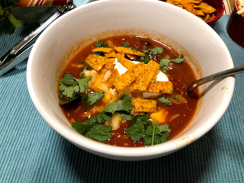 Tortilla soup gumbo topped with cilantro, tortilla strips, sour cream and shredded cheese. Perfect for a warm and hearty dinner.