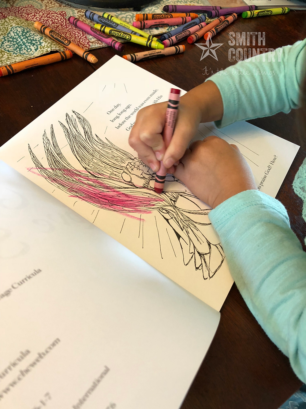 an image of crayons and little hands coloring an image of an Angel.