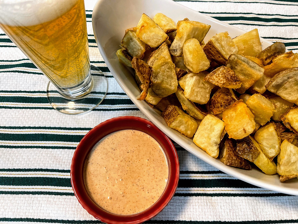 Patatas Bravas in a white dish, remoulade sauce in a red dish and next to a light ale beer (New Glarus Brewing Co Spotted Cow).
