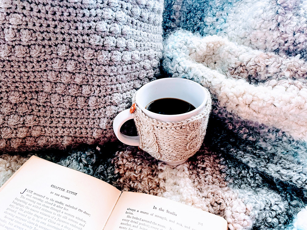Hygge Style image of mug sweater in a cozy blanket and an old book. All images © 2020 Jenn Smith of Smith Country, LLC