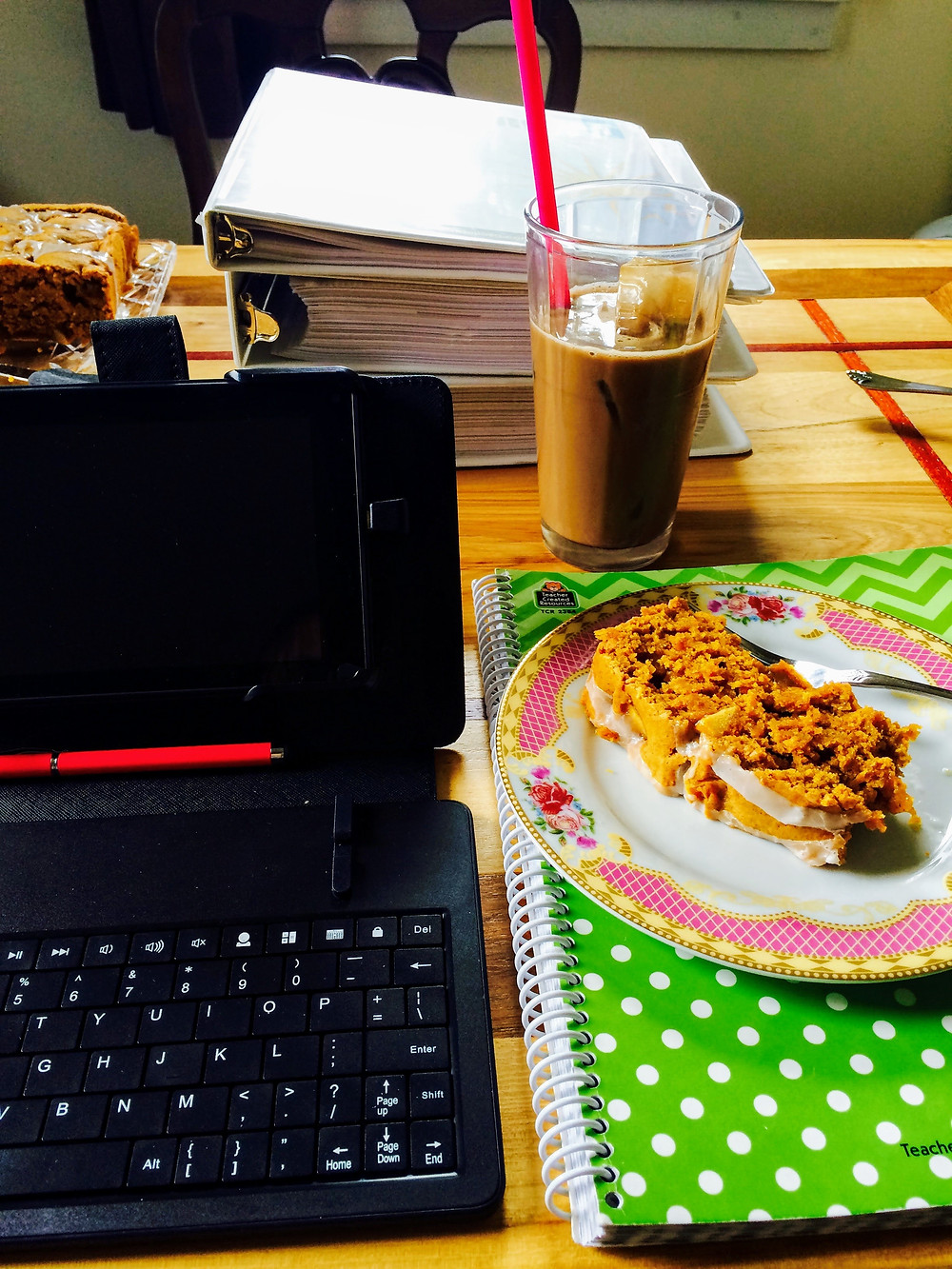 an image of an ice coffee, apple pumpkin bread (ontop of a planner), next to a a small click in tablet and keyboard set.