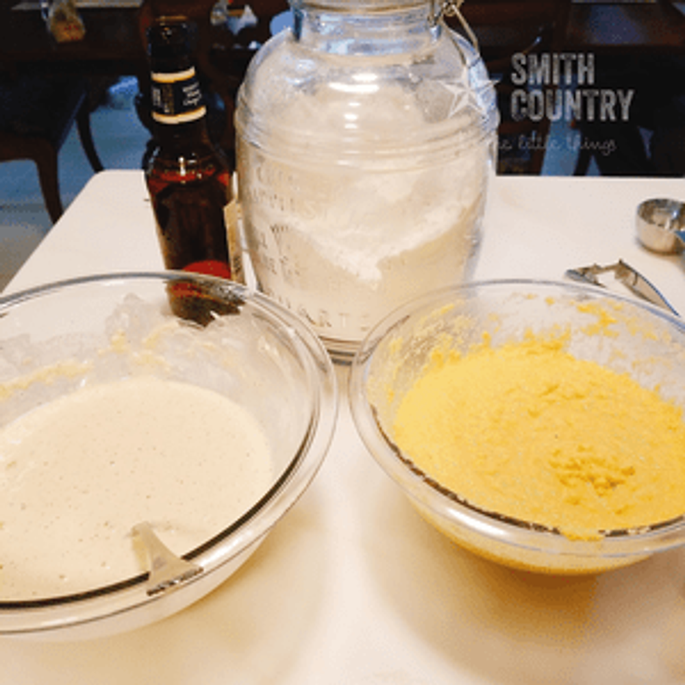 the beer batter next to a bowl of hushpuppy batter. All of this in front of a jar of flour and a glass bottle of beer.