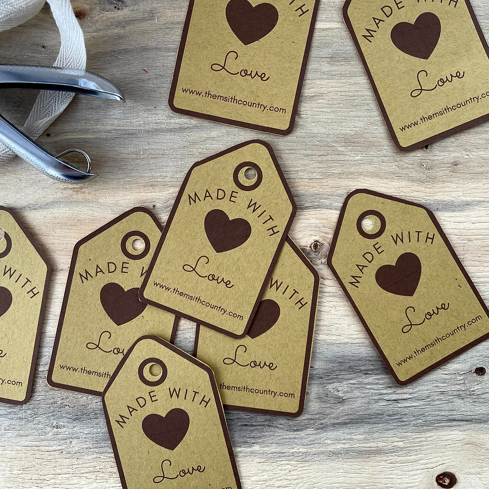 Image of the Made with Love tags. The tags are printed in a Maroon coloring font on a Kraft Paper. A Large heart image between Made with and Love and the bottom of the tag has www.thesmithcountry.com