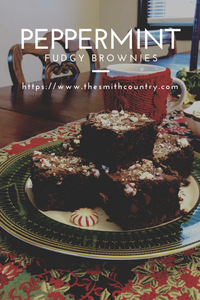 a stack of fudgey brownies on a green plate with peppermint pieces on top of the brownies.