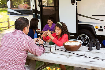 Family outside Camper at Picnic Table