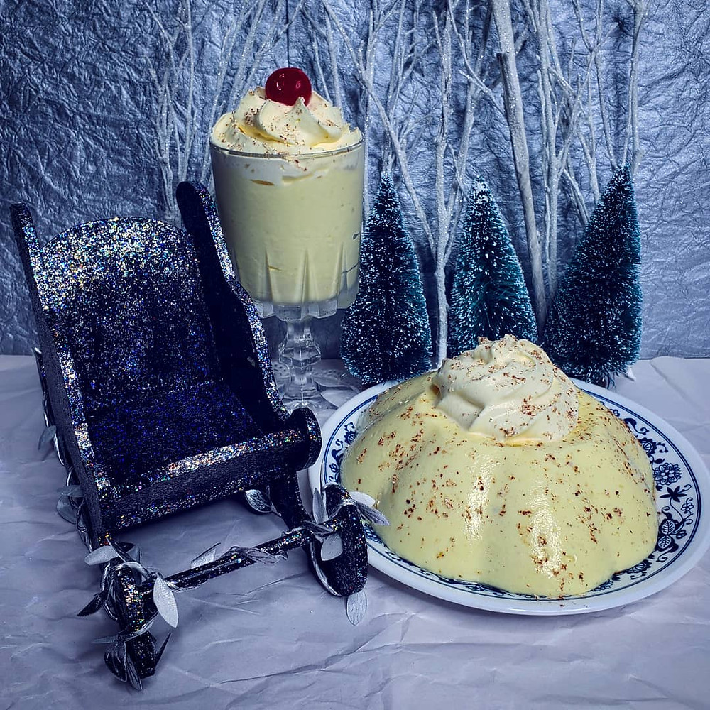 A wintry scene featuring a molded opaque pale yellow gelatin a topped with nutmeg and whipped cream.