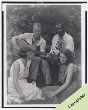 Four musicians including a man playing a guitar, a man playing a violin, and two women seated on ground
