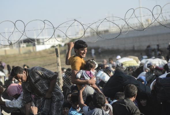 477126896-man-carries-a-girl-as-syrians-fleeing-the-war-pass.jpg.CROP.promovar-mediumlarge