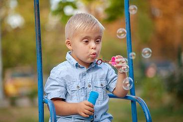 A young boy blows bubbles.