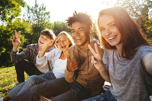 A group of teens sit outside and smile at the camera.