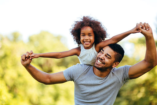 A man lifts a young girl on his back while both smile with thier arms out wide.