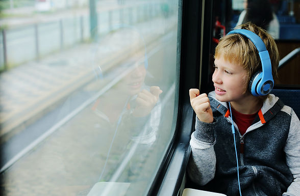 A young boy sits in a train with headphones on.