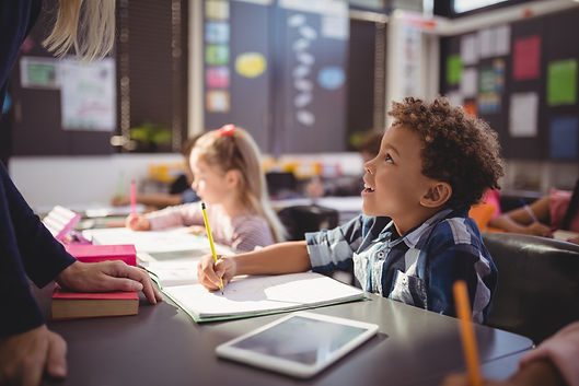 A young student looks up while writing at their desk.