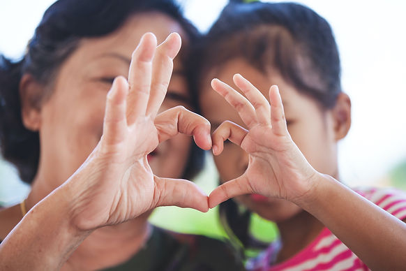 Mother and daughter create a heart shape using their hands.