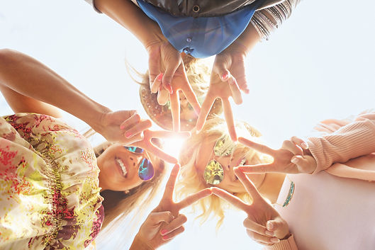 A group of three young adults look down into the camera creating a star with their fingers.