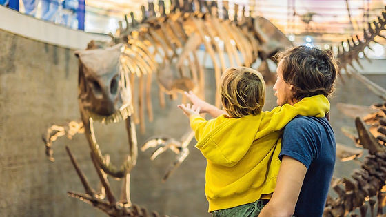 A man carries a young boy as both look at a dinosaur skeleton.