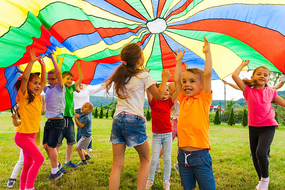 Young children play under a rainbow parachute.