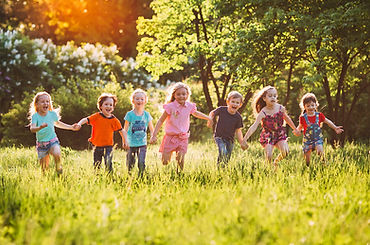 A group of young children hold hands while running on grass.