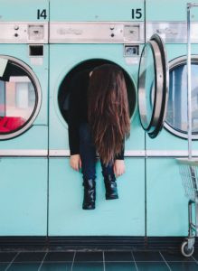 girl hanging out of dryer in laundry mat
