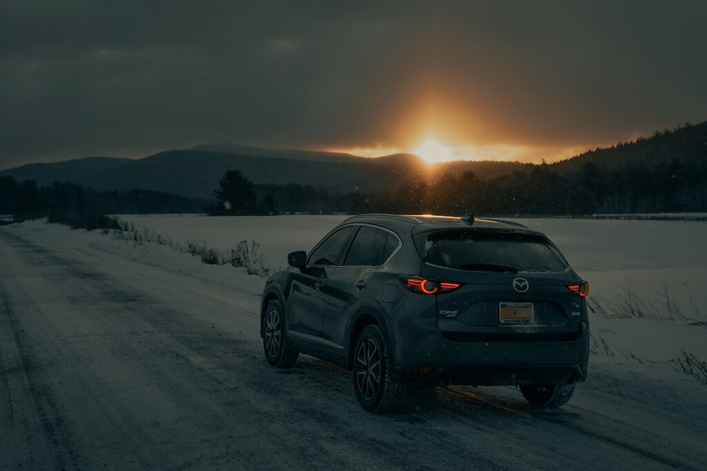 Car driving on snowy road at sunrise