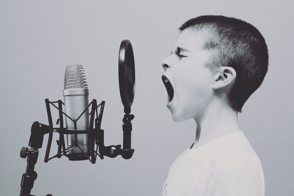 young boy hollering into a microphone