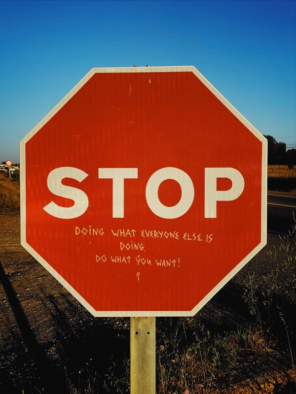 stop sign with note scrawled on bottom