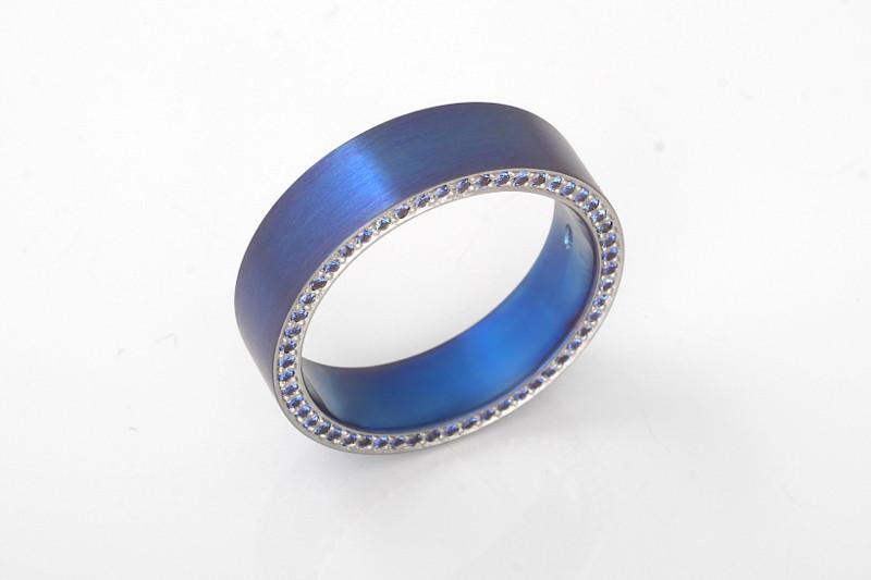 Siniseksi lämpövärjätty titaanisormus, jonka toisella reunalla sinisiä safiireja.