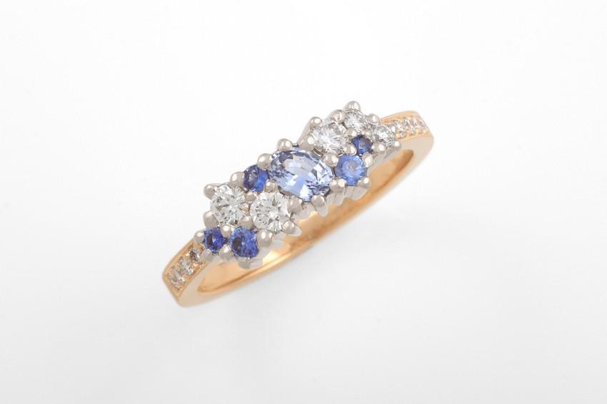 Akvarelli-sormus, jossa kivinä safiireja eri sinisen sävyissä, sekä timantteja.