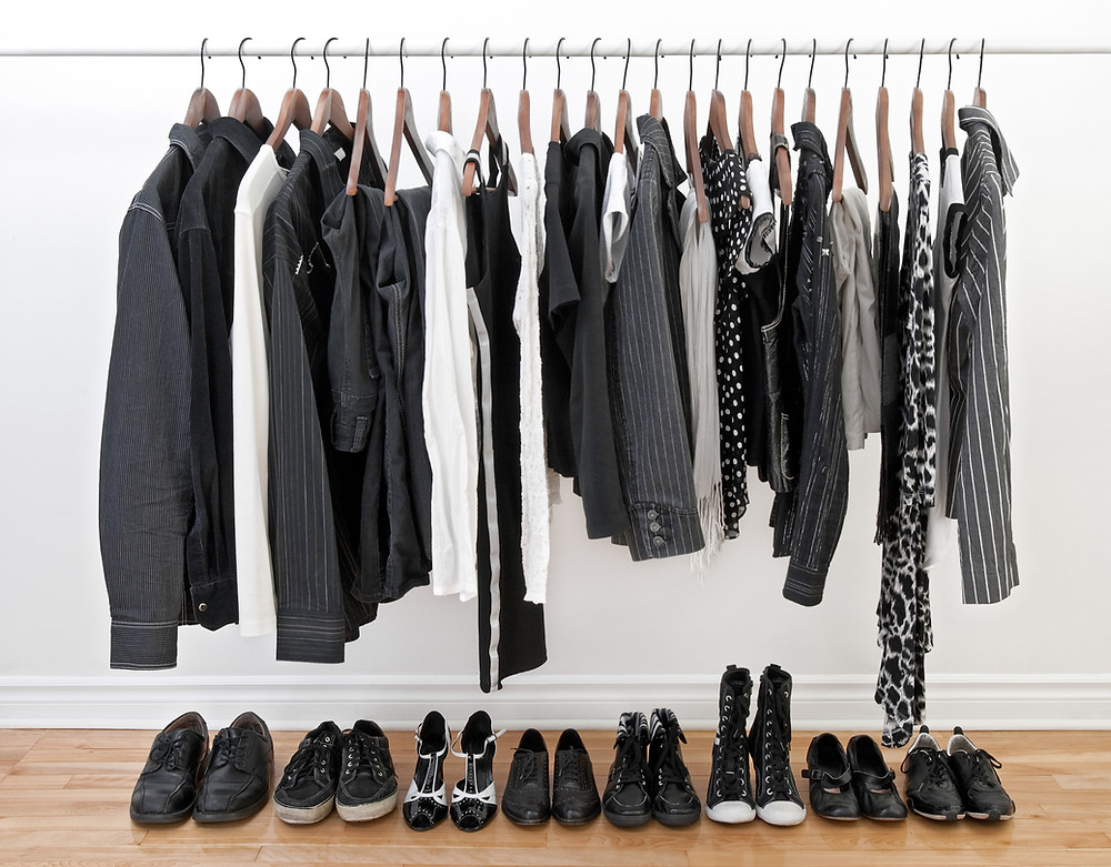 Clothes rack with all black and white clothing.