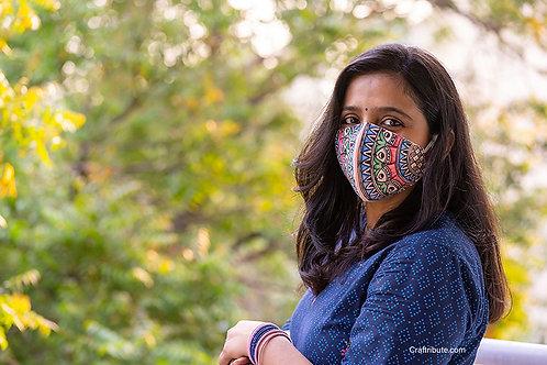 Girl wearing Madhubani design hand painted peach cotton mask with fish design