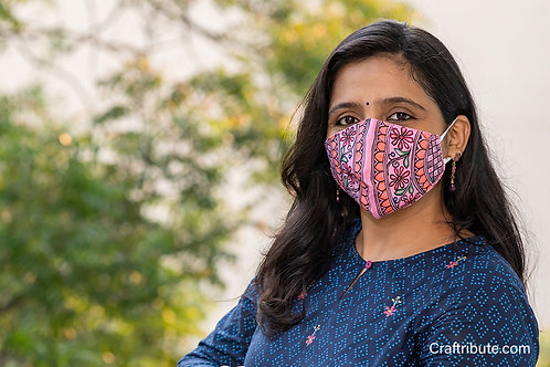 Girl wearing Madhubani design hand painted pink cotton mask with floral design