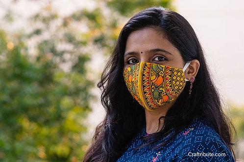 Girl wearing Madhubani design hand painted yellow cotton mask