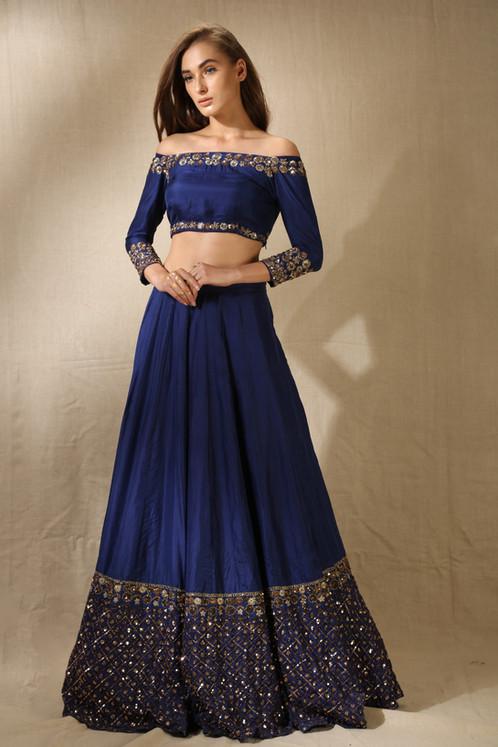 5ceac2dc58b17 A navy lehenga in pure silk with sequins and nakshi border work at hem. It  comes along with a matching navy off shoulder crop top ...