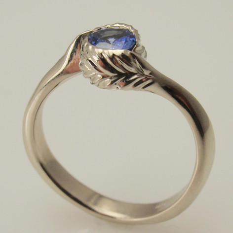 engraved leaf bezel wrapping around a round sapphire.