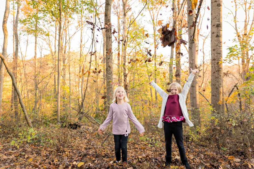 Two girls throwing autumn leaves.