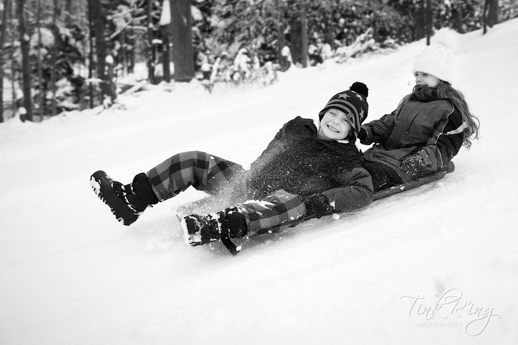 A boy and girl on a sled riding down a hill of snow.
