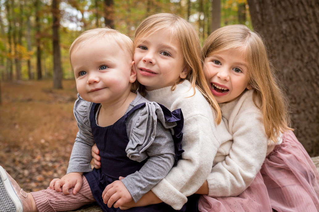 A portrait of three young sisters in the forest.
