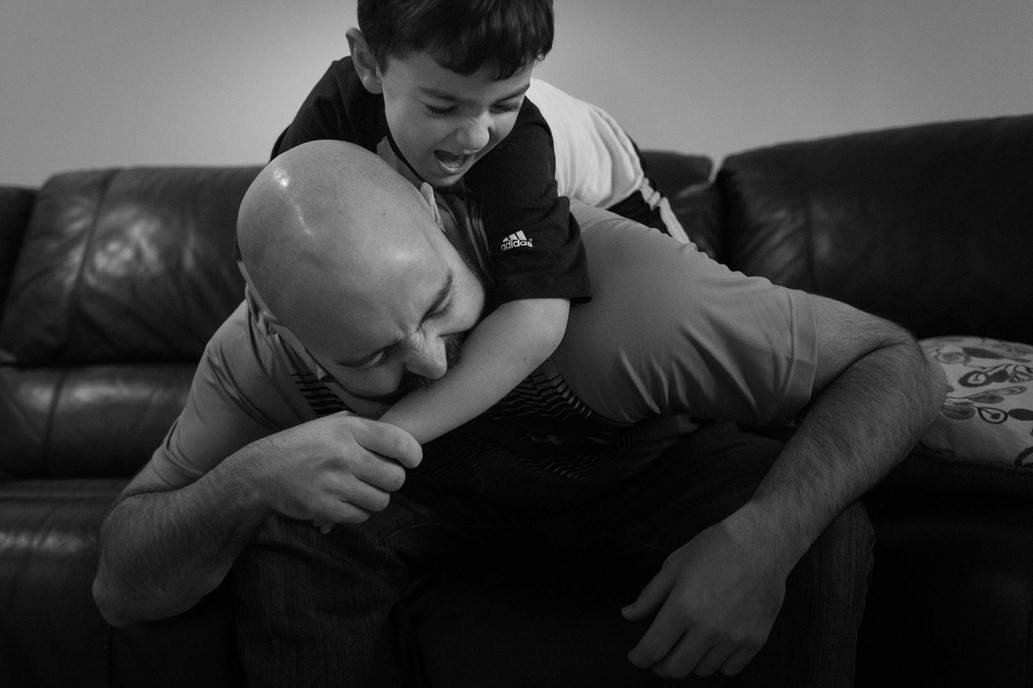 Young boy and dad wrestling.