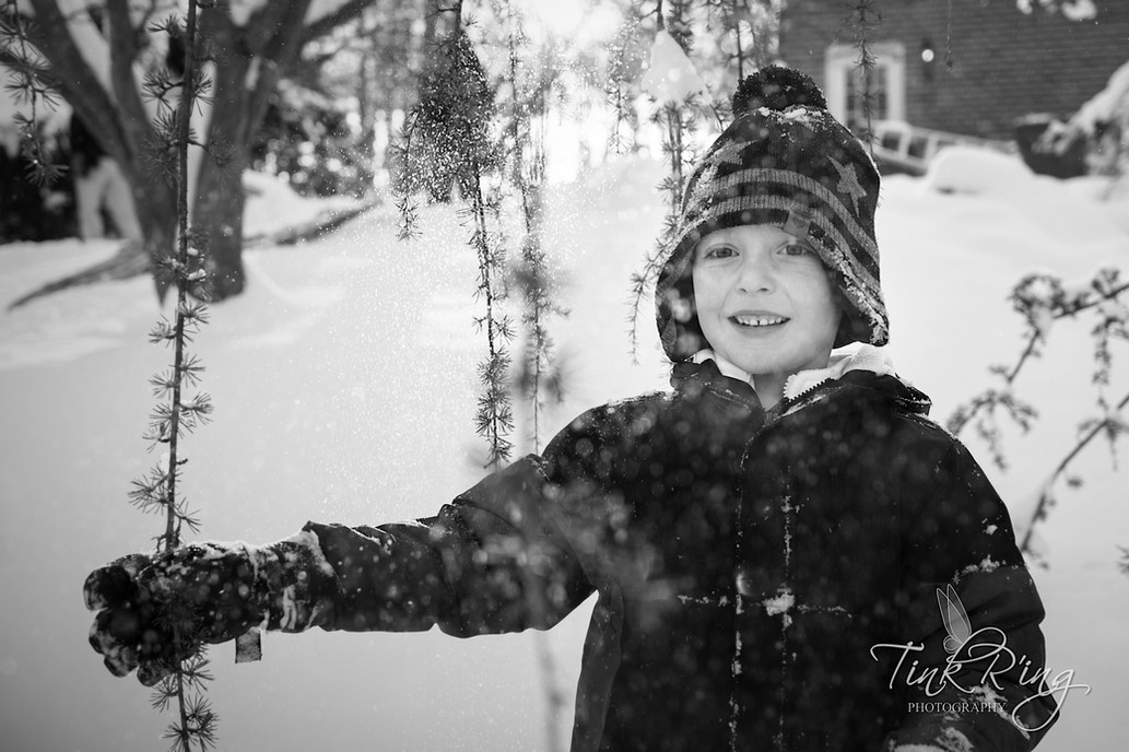 A black and white portrait of a boy in snow.