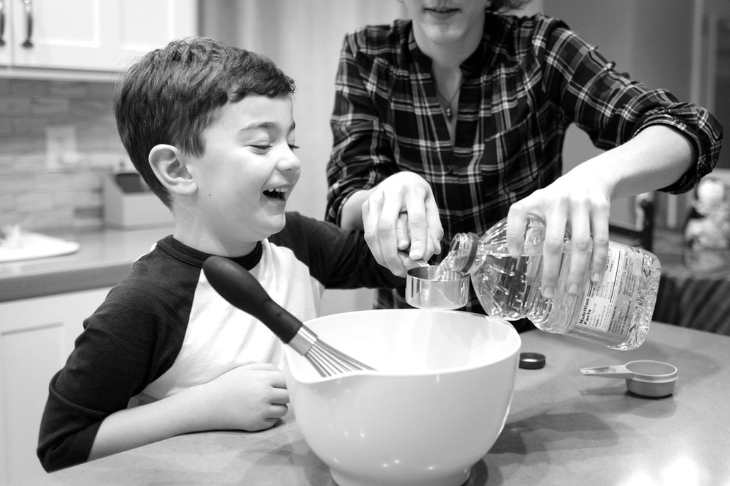 Young boy baking cookies with his mom.