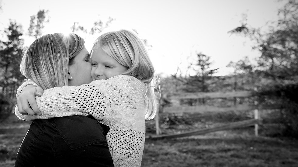 A black and white image of a mother hugging her daughter.