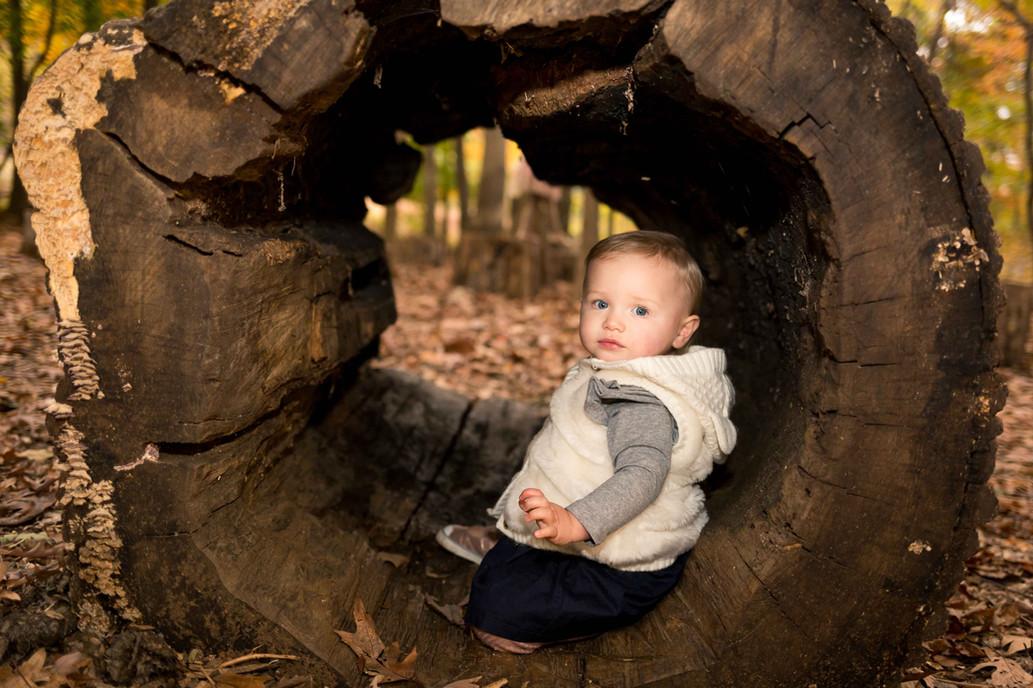 A portrait of a toddler inside a hollow log.