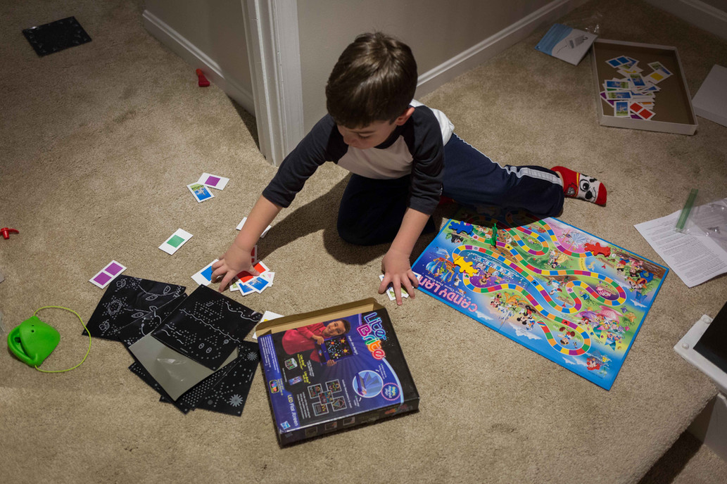 Overhead view of a young boy playing board games.