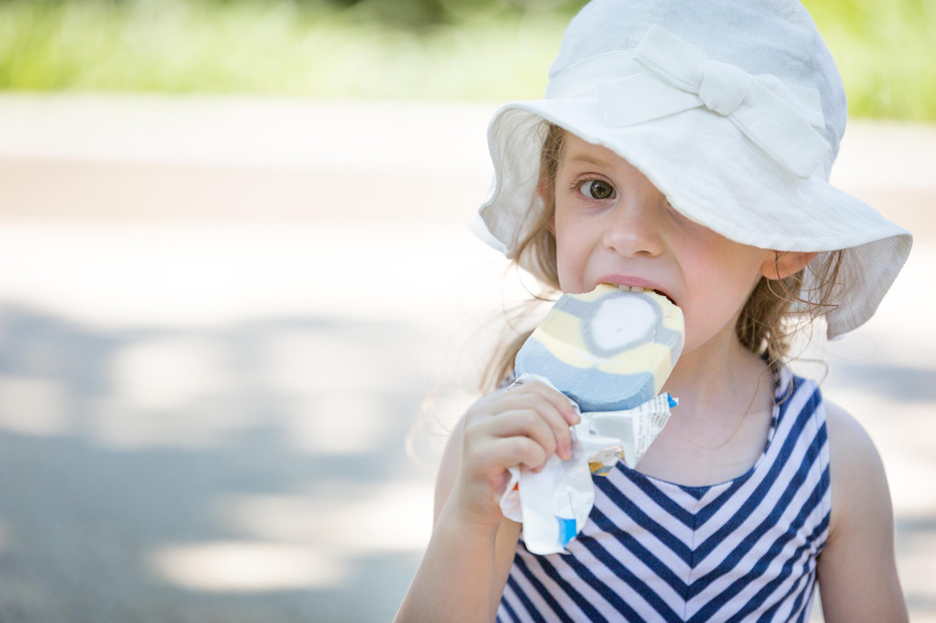 A portrait of a young girl wearing a sun hat and eating icecream.