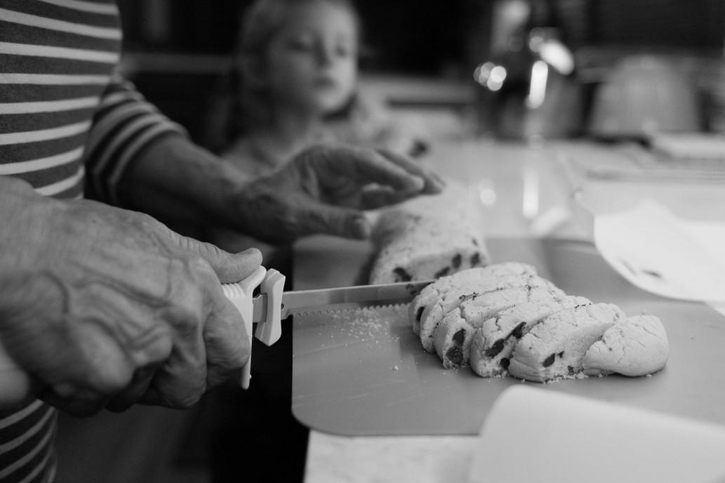 GIrl watching a parent cutting cookie dough.