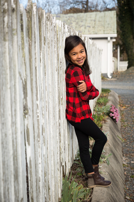 A portrait of a girl leaning on a white picket fence.