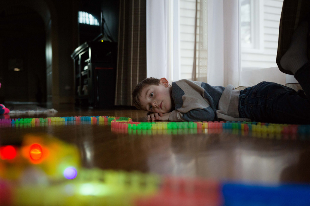 A boy lying on the ground playing with cars.